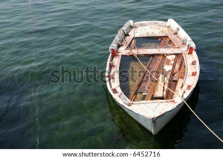 Abandond small wooden boat - stock photo
