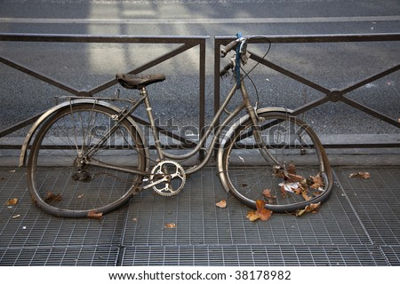 Abandoned and heavily damaged bicycle locked on a fence - stock photo