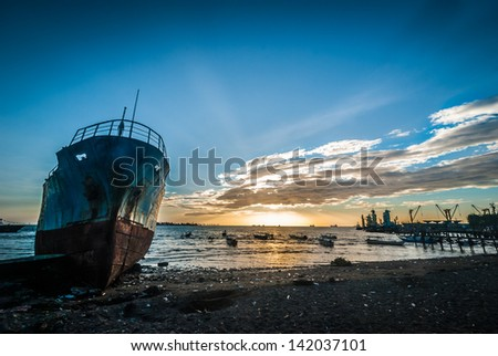 Abandoned and ruined ship in the harbor of Makassar, Indonesia at sunset - stock photo