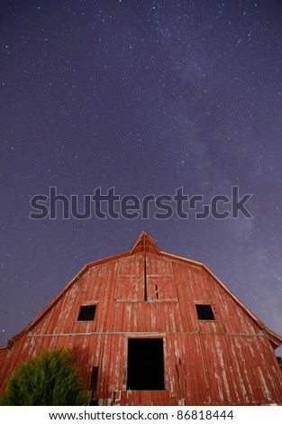 Abandoned barn with the milkyway overhead. - stock photo