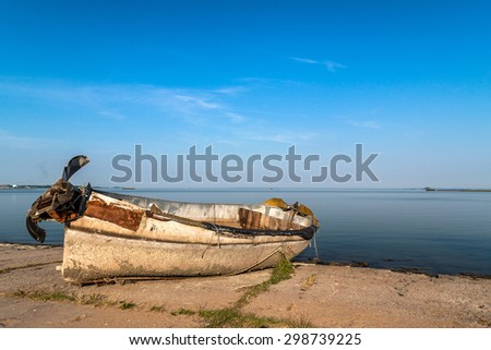 ABANDONED BOAT LAYING ON THE CONCRETE SHORE OF HARBOR - stock photo