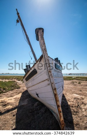 Abandoned boat on the vegetation on the sand dunes of Ria Formosa marshlands located in the Algarve, Portugal.