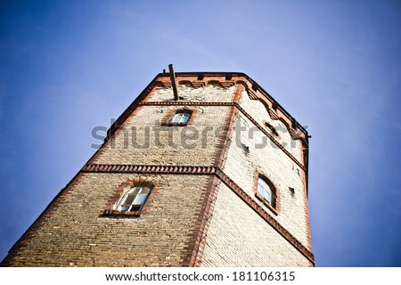 Abandoned brick tower. High building with a blue sky vignette. - stock photo