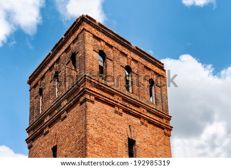 Abandoned brick tower with blue skies and clouds - stock photo