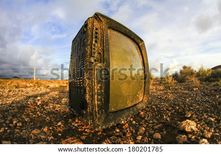 Abandoned Broken Television in the Desert on a Cloudy Day - stock photo