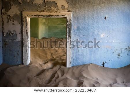 Abandoned building taken over by encroaching sand, Kolmanskop ghost town, Namib Desert - stock photo