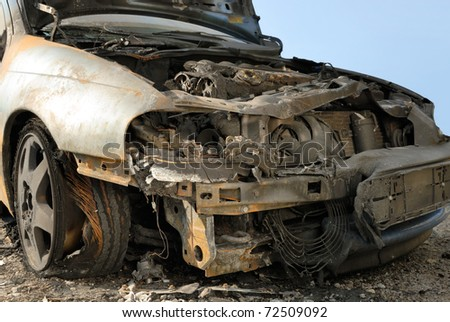 Abandoned burnt down car after an explosion, ready to be scrapped - stock photo