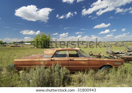 abandoned car in a meadow - stock photo
