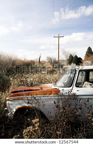 abandoned car with bullet hole through windshield, somewhere in the bushes of Wyoming