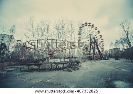 Abandoned carousel and abandoned ferris  at an amusement park in the center of the city of Pripyat, the Chernobyl disaster, the exclusion zone, a ghost town - stock photo