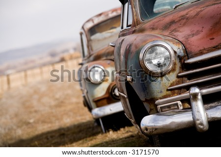 abandoned cars, two vintage cars angled closeup with focus on headlight, rural Wyoming - stock photo