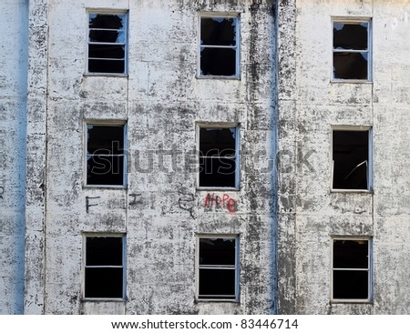 Abandoned cement building with broken windows and 'hope' spray painted on it