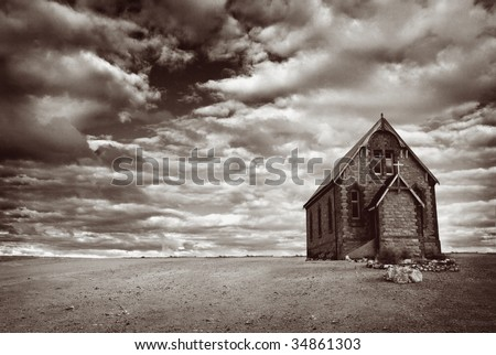 Abandoned church in the desert, with stormy skies.  Monotone image, with added grain. - stock photo