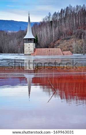 Abandoned church in the middle of a lake full with mining residuals from a copper mine - stock photo