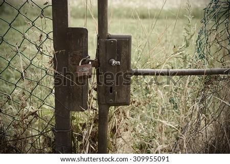 Abandoned closed garden gate. Closeup photo - stock photo