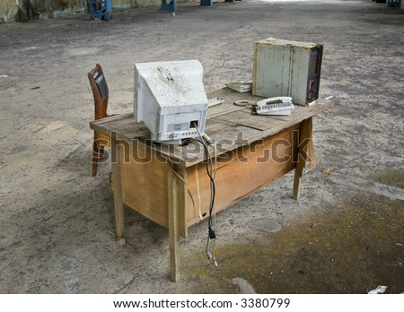 Abandoned computer desk on factory floor - stock photo