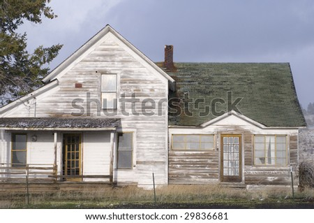 Abandoned derelict farmhouse in eastern (Fox) Oregon under snowing, cloudy skies. - stock photo