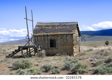 Abandoned, derelict old west jail and gallows out on the alkali plains. - stock photo