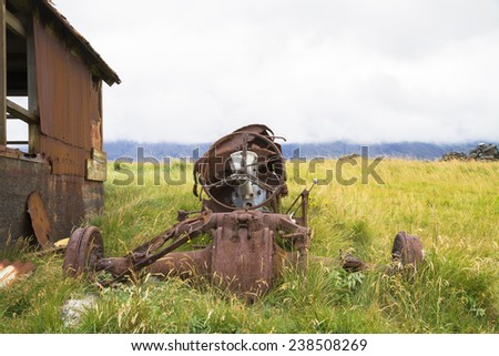 Abandoned derelict tractor in advanced stage of rusting to pieces - stock photo