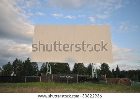 Abandoned drive-in screen with sky and grass - stock photo