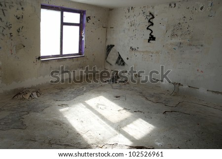 Abandoned empty room with window and light from it - stock photo
