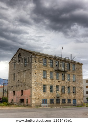Abandoned factory building under cloudy sky - stock photo