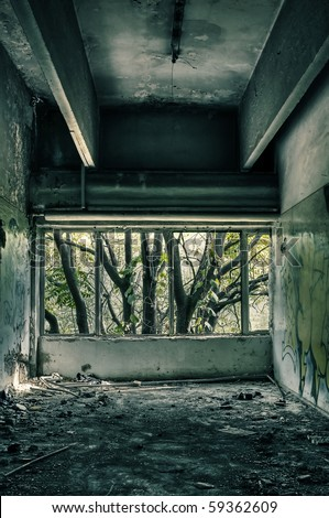 Abandoned factory room, with broken windows and a tree outside the building. - stock photo