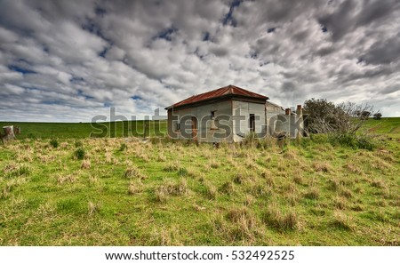 Abandoned farm homestead with corrugated iron roof and walls and boarded up windows left to the elements and now in disrepair