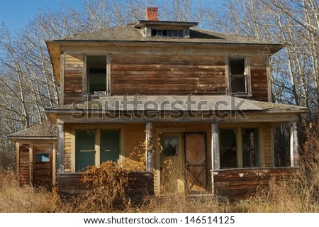 Abandoned farm house  in fall surrounded by small bushes and dry grass  - stock photo