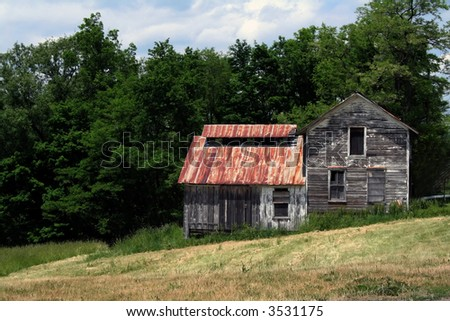 Abandoned farm house with chipped paint and boarded windows