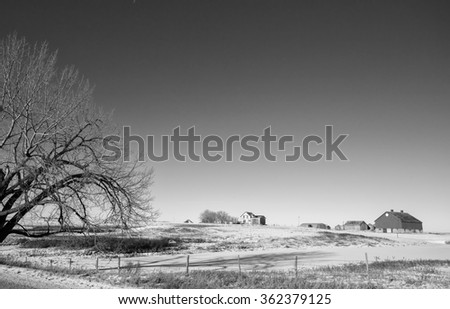 Abandoned farm yard in a rural winter  countryside landscape in black and white - stock photo