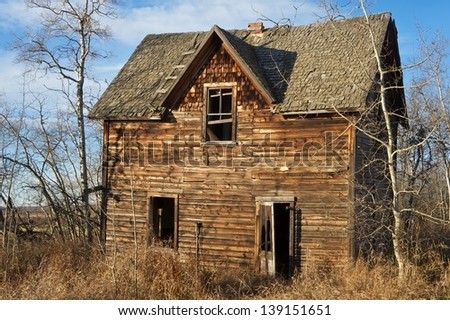 Abandoned farmhouse in dry grass and aspens in fall - stock photo