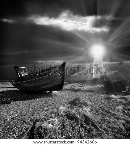 abandoned fishing boat and nets on a shingle beach with a lighthouse illuminating the scene from behind - stock photo