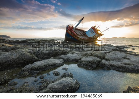 Abandoned fishing boat with beautiful sunset in the east, Thailand - stock photo