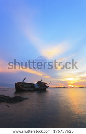 Abandoned fishing boat with beautiful sunset in the east, Thailand