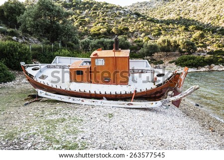 Abandoned fishing trawler on beach at Alonissos, Greece - stock photo