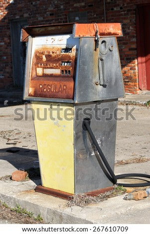 Abandoned gas pump in front of a service station.  Gas stations like this were common in most small communities decades ago, providing gas, oil and repair services for motorists.  - stock photo
