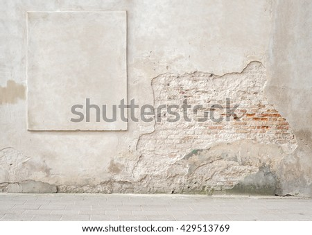 abandoned grunge cracked brick stucco wall with a stucco frame - stock photo