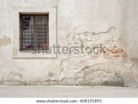 abandoned grunge cracked brick stucco wall with a window grilles - stock photo