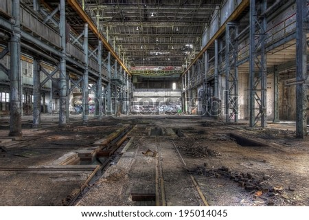 Abandoned hall with many metal carrier and a floating crane - stock photo