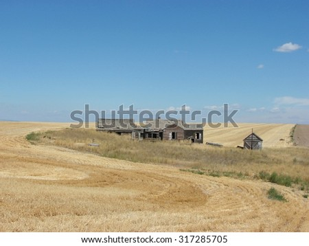 abandoned homestead in harvested field - stock photo