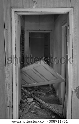 Abandoned house hallway with unhinged door and rubble on dirty floor. Black and white. - stock photo