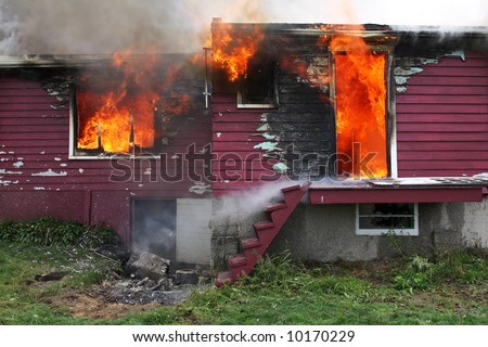 Abandoned house in fire with flames through the windows.  See many more fire and firefighters photo in my portfolio. - stock photo