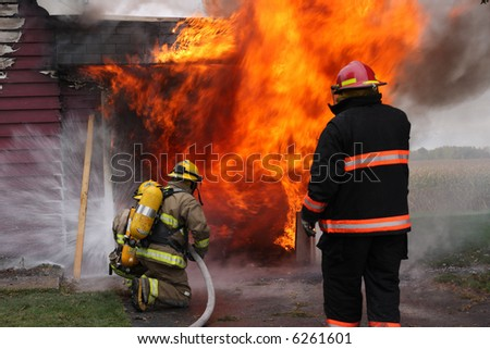 Abandoned house in flame with firefighters in action - stock photo
