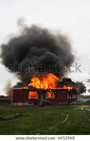 Abandoned house in flame with firefighters in action