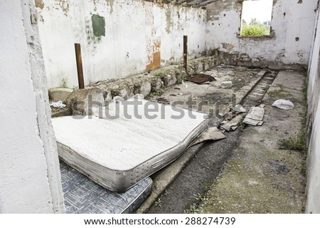 Abandoned house in ruins with mattresses - stock photo