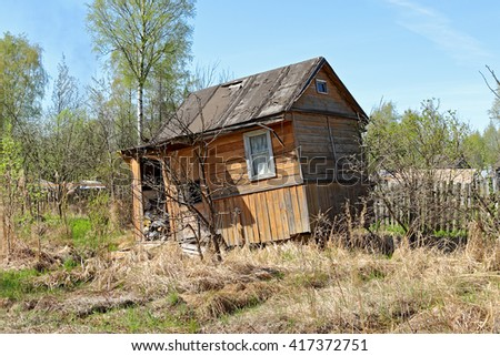 Abandoned house. Old garden plot. A broken fence. poor housing. poverty. rustic. - stock photo