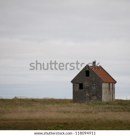 Abandoned house on meadow - stock photo