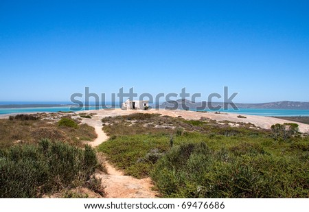 Abandoned house on top of rock hill next to sea. Shot in West Coast National Park, near Langebaan, Western Cape; South Africa - stock photo