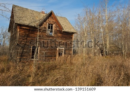 Abandoned house with dry grass and leafless tress - stock photo